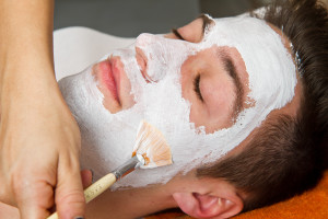Therapist applying a face mask to a beautiful young man in a spa using a cosmetics brush